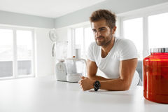 Sport Nutrition. Healthy Man Going To Prepare Shake In Kitchen Royalty Free Stock Images