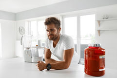 Sport Nutrition. Healthy Man Going To Prepare Shake In Kitchen Royalty Free Stock Photos