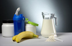 Sport Nutrition Supplement containers with jug of milk Royalty Free Stock Image