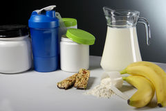 Sport Nutrition Supplement containers with jug of milk Royalty Free Stock Photos