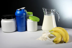 Sport Nutrition Supplement containers with jug of milk Royalty Free Stock Photography