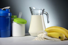 Sport Nutrition Supplement containers with jug of milk Royalty Free Stock Images