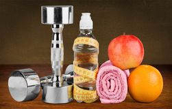 Dumbbells with measuring tape and healthy products stock photo