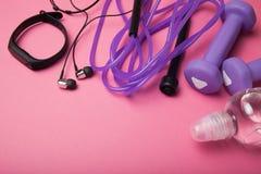 Sport- och friidrott-, hantel- och överhopprep med ett konditionarmband på en rosa bakgrund arkivbilder