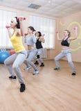 Sport- och konditionbegrepp Fyra yrkesmässiga idrottskvinnor som har böjande övningar för stam med skivstånger Utbildning i sport Arkivfoton