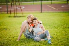 Sport och teknologi Unga förälskade heterosexuella Caucasian par som vilar, efter genomköraren utomhus i har parkerat på gräsmatt royaltyfri fotografi