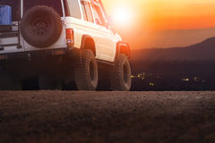 Sport offroad vehicle on dirt field against sun set sky for trav Royalty Free Stock Photography