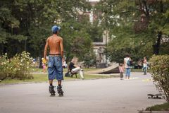Young man is doing roller skates in the park in the city naked to the waist. stock image