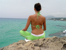 Sport outdoor. Fitness woman sitting on the rocks in yoga pose Stock Photography