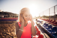Sport outdoor photo of beautiful young blonde woman in pink colorful suit listening to music on headphones by the beach Stock Image