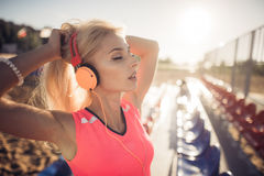 Sport outdoor photo of beautiful young blonde woman in pink colorful suit listening to music on headphones by the beach Royalty Free Stock Photo