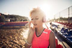 Sport outdoor photo of beautiful young blonde woman in pink colorful suit listening to music on headphones by the beach Stock Photography