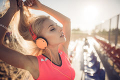 Sport outdoor photo of beautiful young blonde woman in pink colorful suit listening to music on headphones by the beach Stock Images