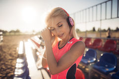 Sport outdoor photo of beautiful young blonde woman in pink colorful suit listening to music on headphones by the beach Royalty Free Stock Image