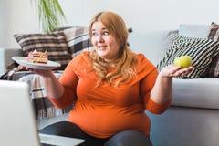 Sport paffuto della donna a casa che si siede esaminando dubbio del dolce fotografia stock
