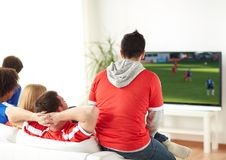 Football fans watching soccer game on tv at home. Sport, people and entertainment concept - friends or football fans watching soccer game on tv at home Stock Image