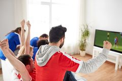 Football fans watching soccer game on tv at home. Sport, people and entertainment concept - happy friends or football fans watching soccer game on tv and Royalty Free Stock Image
