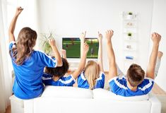 Football fans watching soccer game on tv at home. Sport, people and entertainment concept - happy friends or football fans watching soccer game on tv and Royalty Free Stock Photo