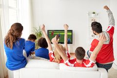 Football fans watching soccer game on tv at home. Sport, people and entertainment concept - happy friends or football fans watching soccer game on tv and Stock Photography
