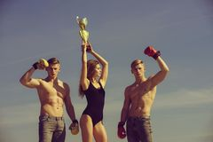 Sport people or team work. Woman and twins with muscular body hold champion cup. Boxer workout and healthy fitness. Men and coach outdoor on blue sky. Winner royalty free stock image