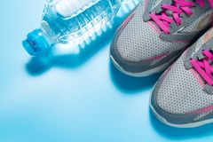 Sport pink shoes and bottle of water on blue background with copyspace for your text. Concept healthy lifestyle and diet.  stock image