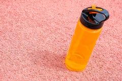 Sport pomarańczowa butelka z wodą pitną na różowi powierzchnię Naturalny pogodny miękki światło zdjęcia stock