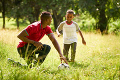 Sport Practice With Father Teaching Son How To Play Soccer. Happy black people doing sport practice in city park. African american family with father teaching Stock Photography