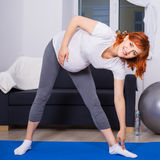 Sport and pregnancy concept - pregnant woman doing stretching ex royalty free stock photo