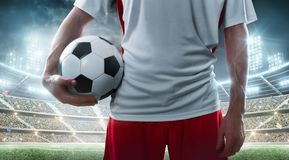 Sport. Professional soccer player holding soccer ball on the stadium background. Close up royalty free stock images