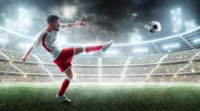 Sport. Professional soccer player kicking a ball. Night 3d stadium with fans and flags. Soccer concept. Soccer action royalty free stock photo