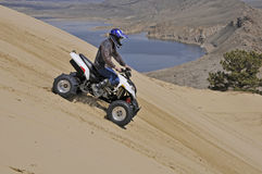 Sport quad. Man riding sand dune mountain on sport quad Stock Photography