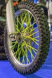 Sport racing motorcycle front wheel with yellow spokes on a blue background Royalty Free Stock Photos