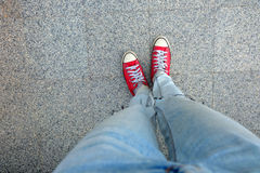 Sport Red Sneakers, Woman legs in Red Sneakers and Blue Jeans Standing on The Cement Background. Great For Any Use Royalty Free Stock Photos