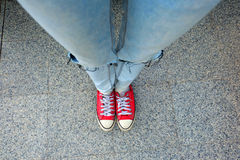Sport Red Sneakers, Woman legs in Red Sneakers and Blue Jeans Standing on The Cement Background. Great For Any Use Stock Photos