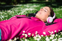 Sport and relax healthy lifestyle. Relaxed female athlete resting and listening music with headphones after workout. Woman lying down on grass and spring flowers Royalty Free Stock Photography
