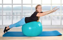 Sport retiree pensioner ball exercise age fit. Senior woman in fitness studio on a ball stock photo
