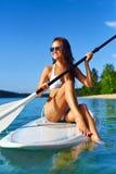 Sport ricreativi La donna sta sull'imbarco della pagaia (praticare il surfing) Immagini Stock Libere da Diritti