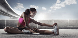 Sport. Runner. Muscular young african woman stretching her leg stock images