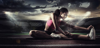Sport. Runner stretching on the running track. The stadium on the background Stock Photos