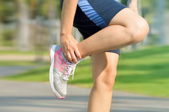 Sport running ankle sprain. Sportswoman touching painful twisted or broken ankle stock photos