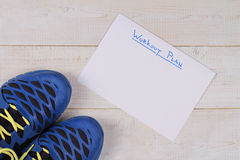 Sport, Running concept. Running shoes and workout plan on white background. Royalty Free Stock Images