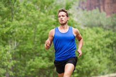 Sport running fitness man training towards goals. Fit male runner sprinting and jogging training outside in forest for marathon run. Muscular handsome Royalty Free Stock Image
