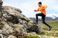 Sport running man in cross country trail run. Fit male runner exercise training and jumping outdoors in beautiful mountain nature landscape with Royalty Free Stock Photo