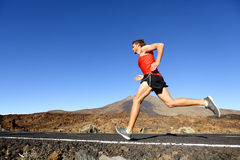 Sport running man - male runner training outdoors. Sprinting on mountain road in amazing landscape nature. Fit handsome jogger working out for marathon outside Stock Photos