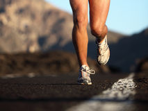 Sport running shoes. In action. Closeup of male runner legs and sports shoes. Fitness man running on mountain road Royalty Free Stock Photos