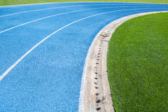 Sport running track blue lane with green field. Curve blue sport running tract with green grass field royalty free stock photos