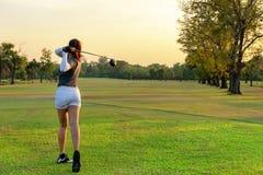 Sport sain Joueur sportif asiatique de golfeur de femme faisant la pièce en t d'oscillation de golf le temps égalisant vert, photos stock
