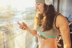 Sport, salute e tecnologia di tema bella sportiva caucasica sexy della donna nella finestra facente una pausa grigia del cappello fotografie stock libere da diritti