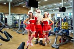 Sport Santa Claus con le ragazze in costumi del ` s di Santa nella palestra sopra immagine stock libera da diritti