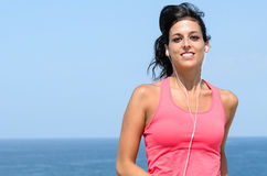 Sport and sea. Portrait of sport woman running with sea and blue sky at the background Stock Photos